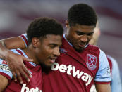 West Ham's Oladapo Afolayan, left, celebrates with West Ham's Ben Johnson after scoring his side's fourth goal during the English FA Cup fourth round soccer match between West Ham United and Doncaster Rovers at the London Stadium in London, Saturday, Jan. 23, 2021. (AP Photo/Ian Walton)
