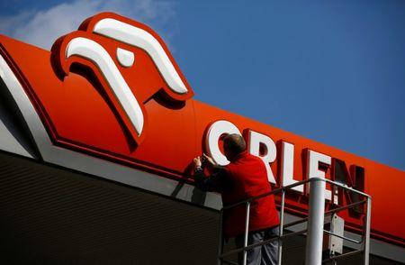 A man fixes PKN Orlen logo, Poland's top oil refiner, at their petrol station in Warsaw