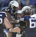 Navy Midshipmen guard E.K. Binns (57) celebrates with teammates after Navy Midshipmen running back DeBrandon Sanders' scored a touchdown in the second half during the Armed Forces Bowl NCAA college football game against the Middle Tennessee Blue Raiders, Monday, Dec. 30, 2013, in Fort Worth. Navy won 24-6. (AP Photo/Matt Strasen)