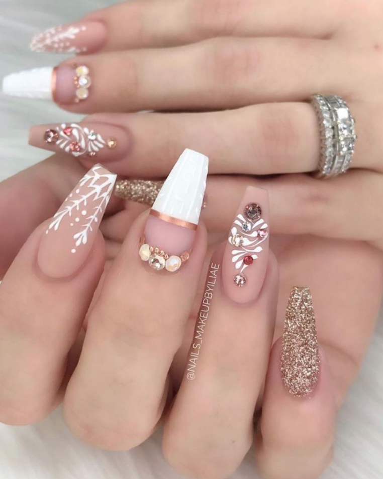"<p>This year, celebrate Christmas in full glam by rocking neutral nail colors decorated with jewels and gold accents inspired by this look from <a href=""https://www.instagram.com/nails_makeupbyiliae/"" rel=""nofollow noopener"" target=""_blank"" data-ylk=""slk:nail artist Enid"" class=""link rapid-noclick-resp"">nail artist Enid</a>.</p><p><a class=""link rapid-noclick-resp"" href=""https://www.amazon.com/11440pcs-Rhinestones-Teenitor-professional-Decoration/dp/B07RJRV71H?tag=syn-yahoo-20&ascsubtag=%5Bartid%7C10072.g.34113691%5Bsrc%7Cyahoo-us"" rel=""nofollow noopener"" target=""_blank"" data-ylk=""slk:SHOP NAIL JEWELS"">SHOP NAIL JEWELS</a></p>"