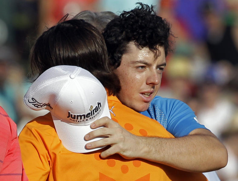 Rory McIlroy, of Northern Ireland, right, embraces Rickie Fowler, left, after Fowler defeated McIlroy and D.A. Points on the first playoff hole to win the Wells Fargo Championship golf tournament at Quail Hollow Club in Charlotte, N.C., Sunday, May 6, 2012. (AP Photo/Chuck Burton)