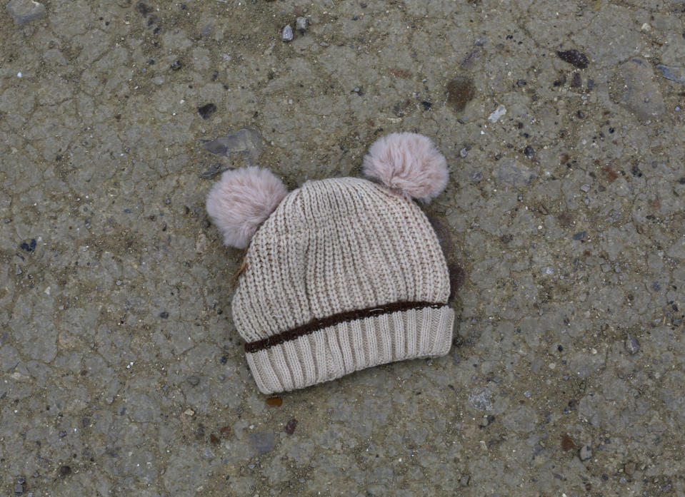 FILE - In this March 28, 2021, file photo, a child's knitted cap lies on the ground near the banks of the Rio Grande river in Roma, Texas. For the third time in seven years, U.S. officials are scrambling to handle a dramatic spike in children crossing the U.S.-Mexico border alone, leading to a massive expansion in emergency facilities to house them as more kids arrive than are being released to close relatives in the United States. (AP Photo/Dario Lopez-Mills, File)
