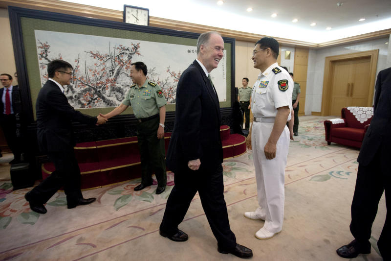 U.S. National Security Adviser Tom Donilon, center, walks to his seat while Gen. Fan Changlong, vice chairman of China's Central Military Commission, back right, shakes hands with U.S. Ambassador Gary Lock, during their meeting at the Bayi Building, headquarters of Chinese Defense Ministry, in Beijing Tuesday, May 28, 2013. Gen. Sun Jianguo, right, Chinese People's Liberation Army (PLA) Deputy Chief of General Staff, also waits to shake hands with visiting U.S. officials. (AP Photo/Alexander F. Yuan, Pool)