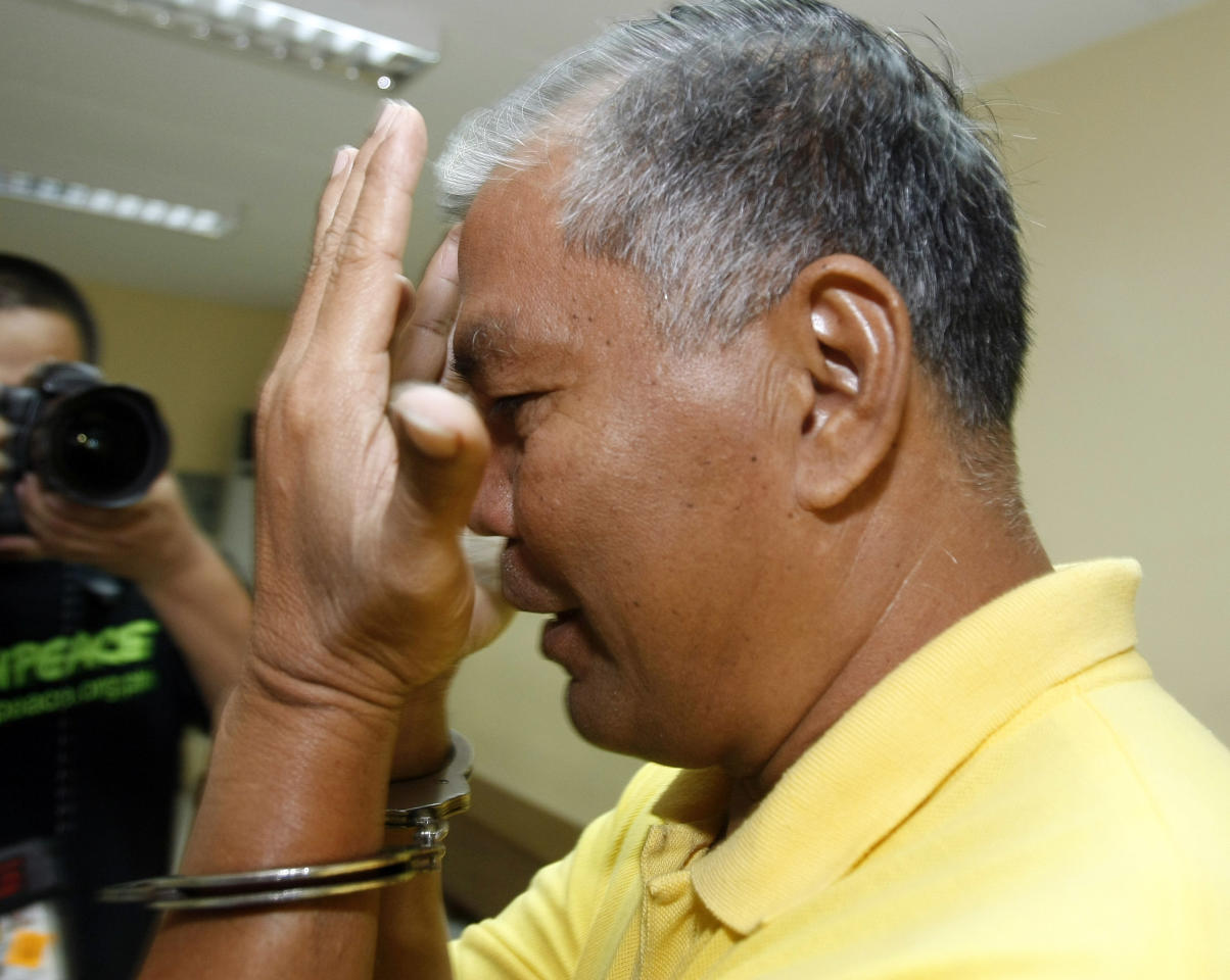 A handcuffed suspect in the massacre of 57 people, including 32 journalists and staff, in Maguindanao province in southern Philippines, tries to shield his face from the media as he attends the continuing trial at Camp Bagong Diwa in Taguig city, east of Manila, Philippines on the 2nd anniversary of the massacre Wednesday Nov. 23, 2011. Andal Ampatuan Sr., patriarch of a powerful Maguindanao clan and former governor of an autonomous Muslim region, is among nearly 100 suspects being tried on murder charges in the massacre, together with his sons and relatives. (AP Photo/Bullit Marquez)