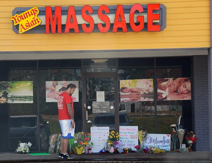 Marcus Lyon, 31, looks at flowers and other memorial items left at the scene of a shooting in Acworth, Georgia. Lyon was inside the Young's Asian Massage spa on March 16 when the shooter came in, and Lyon ducked behind a massage table to hide.
