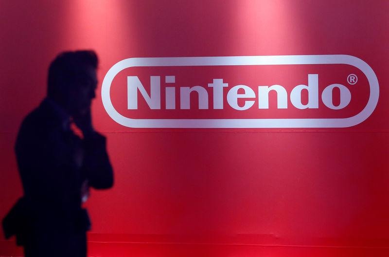 A man stands in front of Nintendo's logo at the presentation ceremony of its new game console Switch in Tokyo