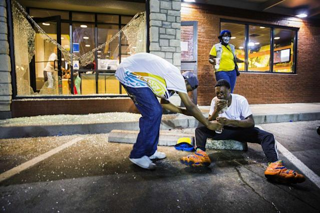<p>Protesters react to the effects of tear gas which was fired at demonstrators reacting to the shooting of Michael Brown in Ferguson, Missouri August 17, 2014. Shots were fired and police shouted through bullhorns for protesters to disperse, witnesses said, as chaos erupted Sunday night in Ferguson, Missouri, which has been racked by protests since the unarmed black teenager was shot by police on August 9. (Lucas Jackson/Reuters) </p>