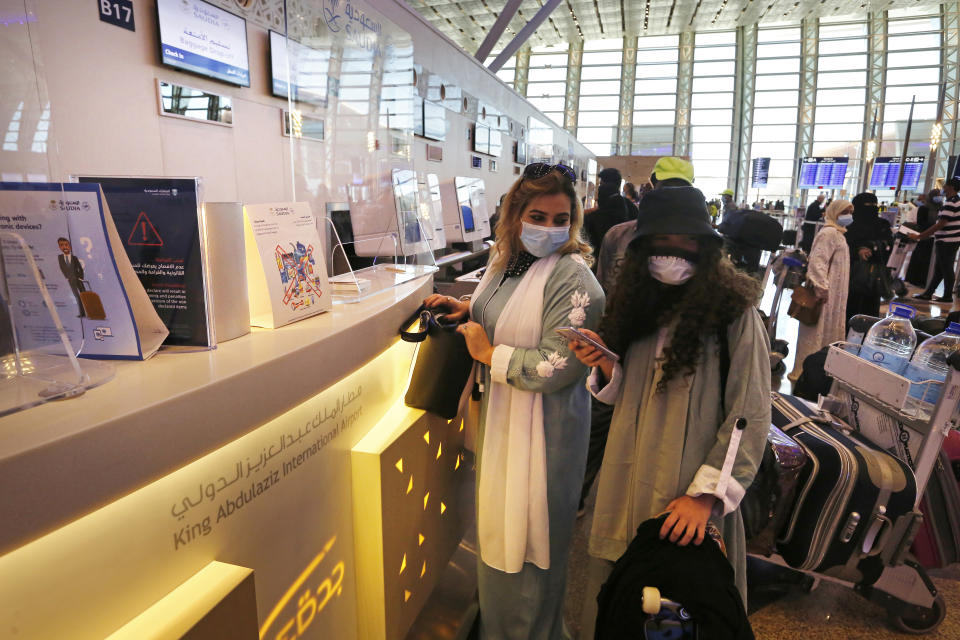 In this May 17, 2021 photo, Saudi passenger Safinaz Abdel Gawwad, left, checks her baggage before boarding a flight to Egypt for tourism, at King Abdulaziz International Airport in Jiddah, Saudi Arabia. The cloud of social restrictions that loomed over generations of Saudis is quickly dissipating and the country is undergoing visible change. Still, for countless numbers of people in the United States and beyond, Saudi Arabia will forever be associated with 9/11. (AP Photo/Amr Nabil)