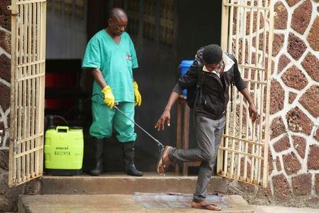 A health worker sprays a visitor with chlorine after leaving the isolation facility, prepared to receive suspected Ebola cases, at the Mbandaka General Hospital, in Mbandaka, Democratic Republic of Congo May 20, 2018. REUTERS/Kenny Katombe/File Photo