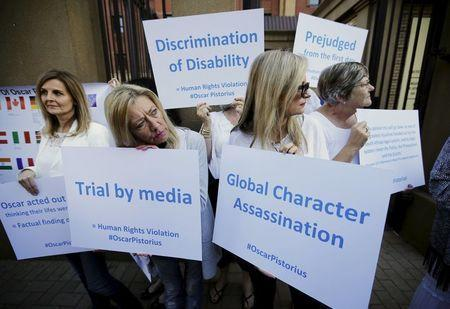 Supporters of South African Olympic and Paralympic sprinter Oscar Pistorius hold placards outside the North Gauteng High Court in Pretoria before a brief appearance by Pistorius, April 18, 2016. REUTERS/Mike Hutchings