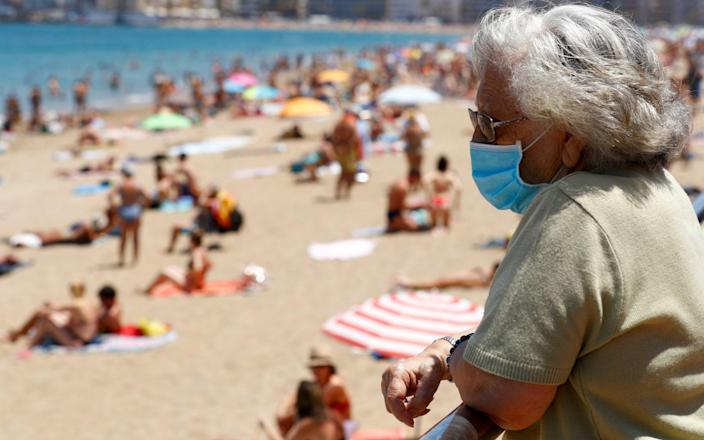 Woman wearing a face mask on the beach in Spain - Reuters