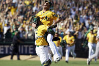 Oakland Athletics relief pitcher Grant Balfour, top, and catcher Derek Norris celebrate after their 12-5 win over the Texas Rangers in a baseball game, Wednesday, Oct. 3, 2012 in Oakland, Calif. The A's clinched the AL West title with the win. (AP Photo/Ben Margot)
