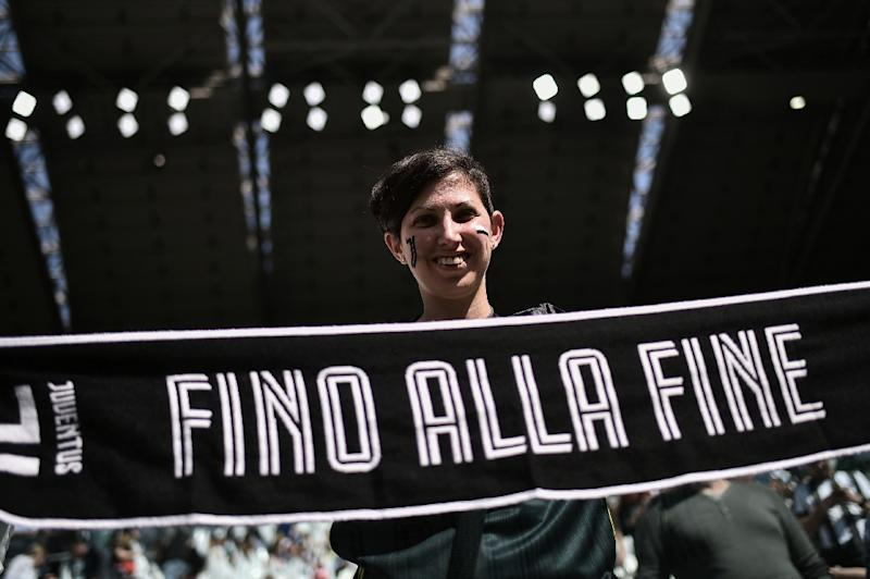 "A Juventus fan displays a scarf reading ""Until the end"" prior to the Women's Serie A football match against Fiorentina. (AFP Photo/Marco BERTORELLO                    )"