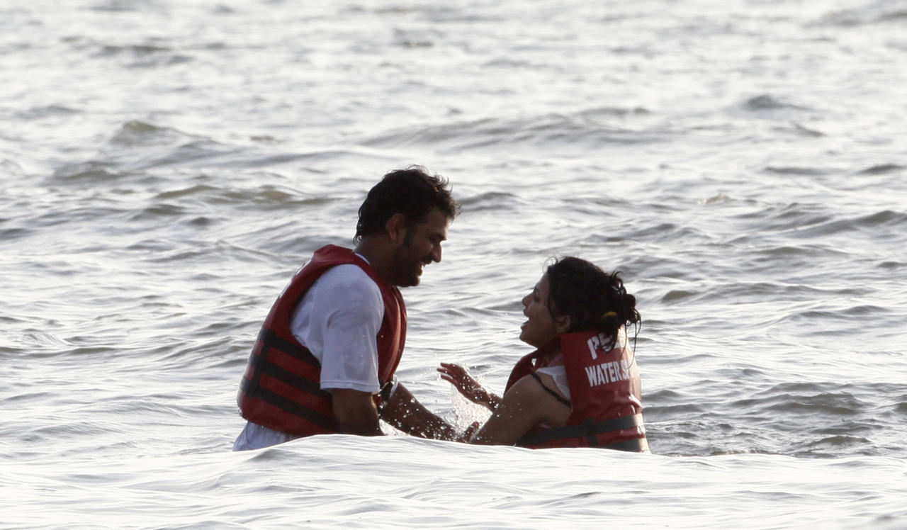 India's captain Mahendra Singh Dhoni, left, and his wife Sakshi spend time in the Arabian sea after India won the three one international cricket series against Australia, in Goa, India, Sunday, Oct. 24, 2010. The third and final limited-overs international between India and Australia was abandoned without a ball being bowled due a wet outfield at the Nehru Stadium in Goa on Sunday.