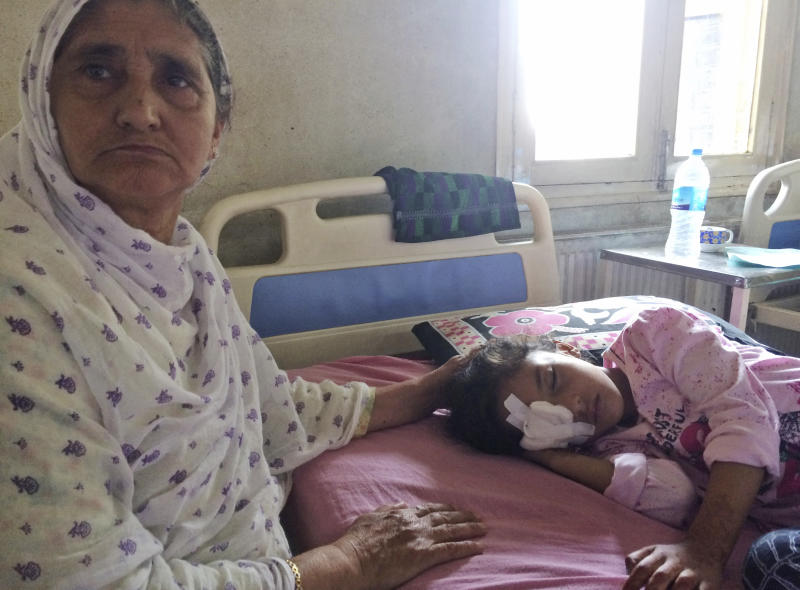Grandmother Sara Ali, attends to six year old Kashmiri girl Muneefa Nazir, at a hospital after she was wounded by a marble shot from a sling used by Indian paramilitary soldiers in Srinagar Indian controlled Kashmir, Tuesday, Aug. 13, 2019.  Indian Prime Minister Narendra Modi defended his government's controversial measure to strip the disputed Kashmir region of its statehood and special constitutional provisions in an Independence Day speech Thursday, as about 7 million Kashmiris stayed indoors for the 11th day of an unprecedented security lockdown and communications blackout. (AP Photo/ Aijaz Hussain)