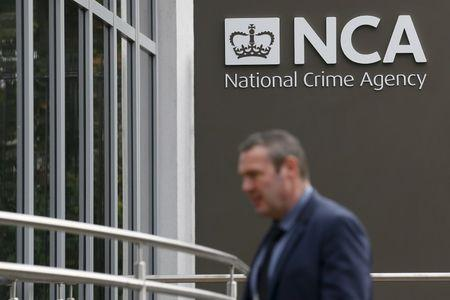 A pedestrian walks past the National Crime Agency headquarters in London