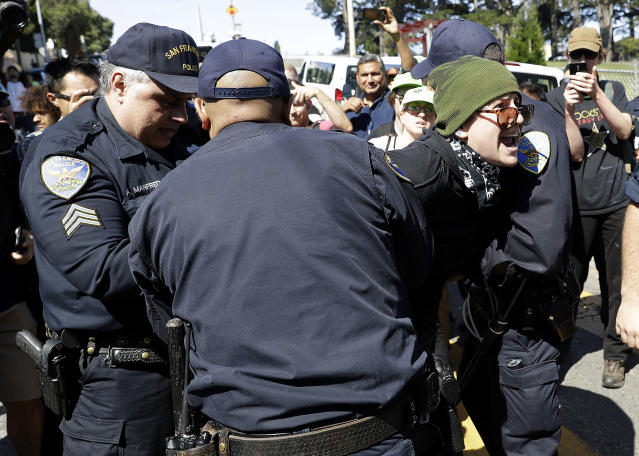 <p>San Francisco Police Officers arrest a protester outside of Alamo Square Park in San Francisco, Saturday, Aug. 26, 2017. San Francisco officials took further steps Saturday to prevent violence ahead of a planned news conference by a right-wing group. Officials erected fencing and a large contingent of police monitored Alamo Square park, where the group Patriot Prayer was set to hold its event. (Photo: Marcio Jose Sanchez/AP) </p>