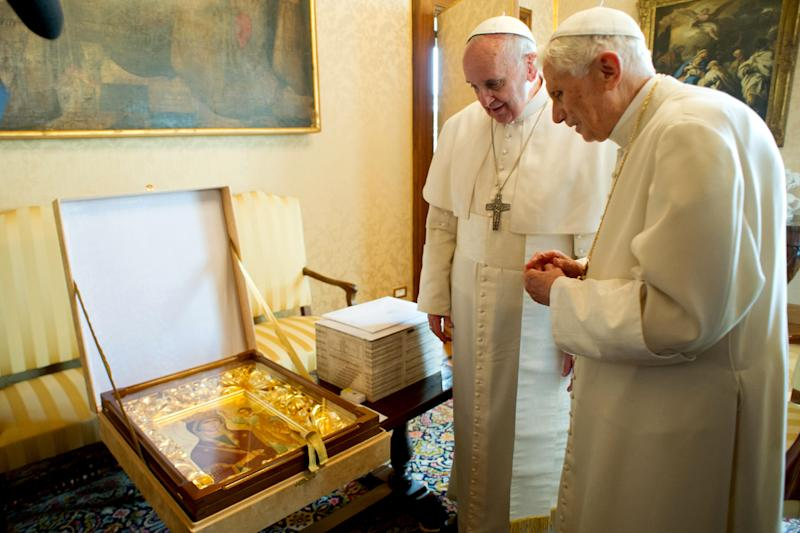 """In this photo provided by the Vatican paper L'Osservatore Romano, Pope Francis, left, and Pope emeritus Benedict XVI meet in Castel Gandolfo Saturday, March 23, 2013. Pope Francis has traveled to Castel Gandolfo to have lunch with his predecessor Benedict XVI in a historic and potentially problematic melding of the papacies that has never before confronted the Catholic Church. The Vatican said the two popes embraced on the helipad. In the chapel where they prayed together, Benedict offered Francis the traditional kneeler used by the pope. Francis refused to take it alone, saying """"We're brothers,"""" and the two prayed together on the same one. (AP Photo/Osservatore Romano, HO)"""