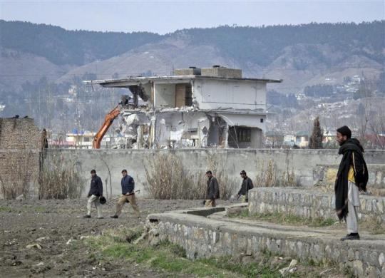 Policemen walk past while demolition work is carried out on the building where al Qaeda leader Osama bin Laden was killed by U.S. special forces last May, in Abbottabad February 26, 2012. Pakistani forces began demolishing the house where al Qaeda leader Osama bin Laden was killed by U.S. special forces, in an unexplained move carried out in the dark of night.