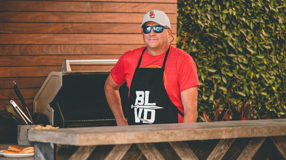 "USC coach Clay Helton wears an apron that says ""BLVD"" as he stands at an outdoor grill."