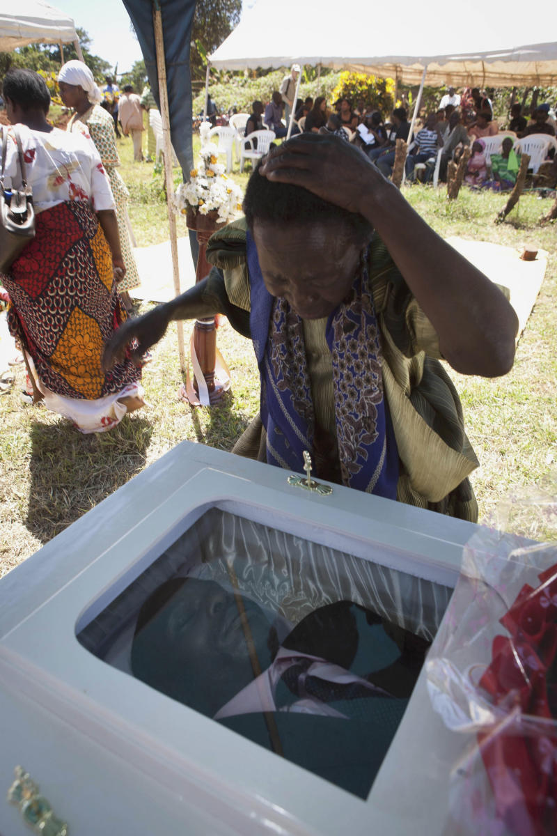 "A woman reacts after viewing the coffin of Ugandan gay activist, David Kato at Mukono, Uganda, Friday, Jan. 28, 2011. A prominent Ugandan gay rights activist whose picture was published by an anti-gay newspaper next to the words ""Hang Them"" was bludgeoned to death. Police said Thursday his sexual orientation had nothing to do with the killing and that one ""robber"" had been arrested. (AP Photo/Michele Sibiloni)"