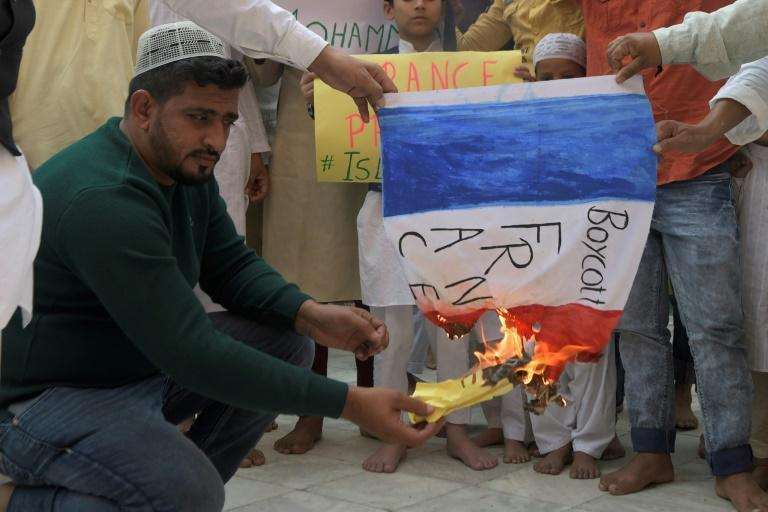 Muslim devotees burn a French national flag during a demonstration to protest against French President Emmanuel Macron in India.