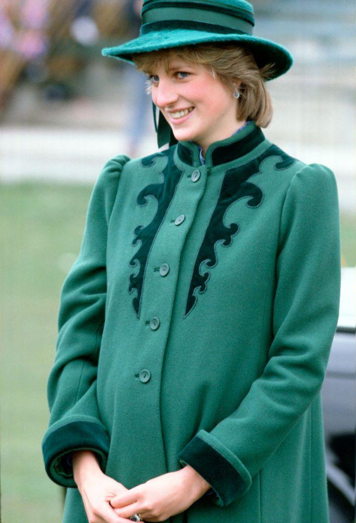 <p>Lady Di cradles her bump while pregnant with Prince William. This wool green coat shares similar velvet detailing with her headwear.</p>