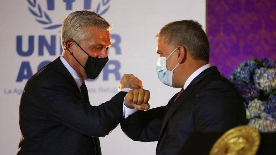 "The United Nations High Commissioner for Refugees (UNHCR) Filippo Grandi bumps elbows with Colombia""s President Ivan Duque during the announcement of the granting of legal status of temporary protection to Venezuelan migrants, in Bogota, Colombia February 8, 2021."