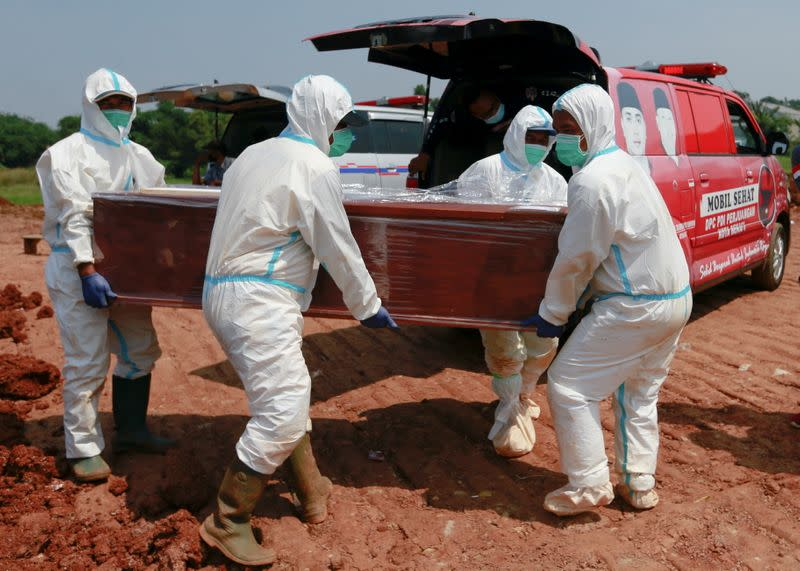 Gravediggers work at Muslim burial area for COVID-19 victims provided by government, in Bekasi