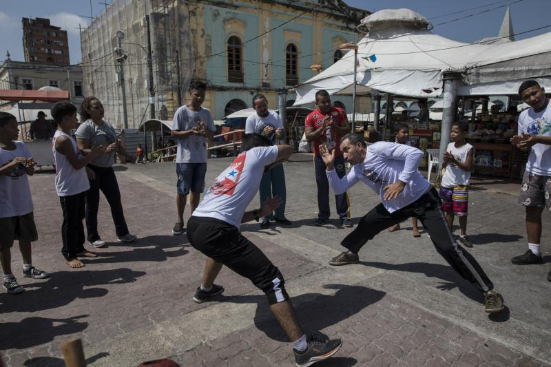 In this Sept. 1, 2019 photo, people practice capoeira at the Ver-o-Peso riverside market in Belém, Brazil. Capoeira is an Afro-Brazilian martial art that combines elements of dance, acrobatics and music. It was developed by enslaved Africans in Brazil. (AP Photo/Rodrigo Abd)