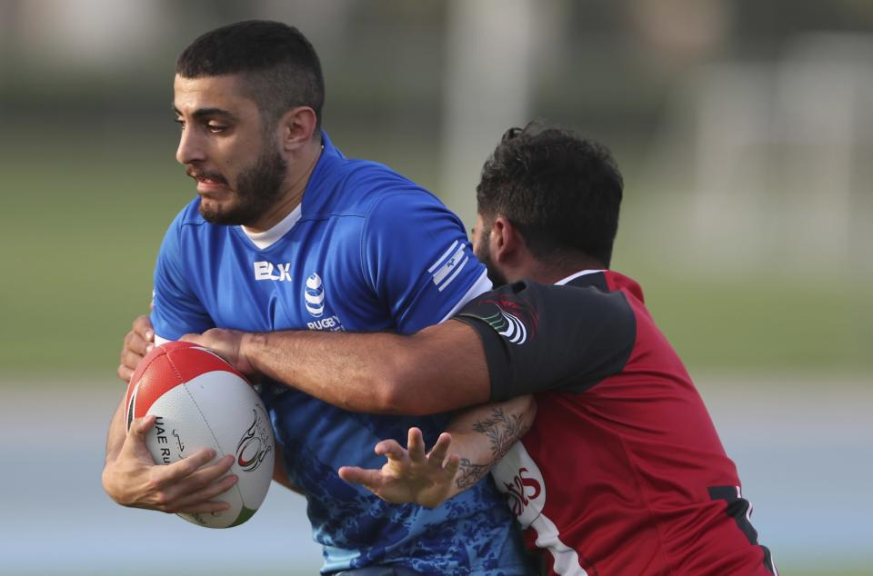 Israel's Amir Fawarsa, left, is tackled bu UAE player during a friendly match in Dubai, United Arab Emirates, Friday, March 19, 2021. (AP Photo/Kamran Jebreili)