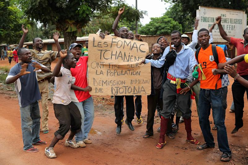 """Christians hold up a sign that reads: """"Chadian FOMAC Fired on the Population. Djotona Must Resign Immediately"""", as they protest against the presence of Chadian troops within the FOMAC forces in Bangui, Central African Republic, Tuesday Dec. 10, 2013. Two French soldiers were killed in combat in Central African Republic's capital, the first French casualties since French President Francois Holland ordered a stepped-up military presence in the restive former colony to help quell inter-religious violence. (AP Photo/Jerome Delay)"""