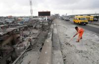 A worker cleans a street in Lagos