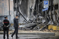 Carabinieri officers stand on the site of a plane crash, in San Donato Milanese suburb of Milan, Italy, Sunday, Oct. 3, 2021. According to media reports, a small plane carrying five passengers and the pilot crashed into an apparently vacant office building in a Milan suburb. Their fates were not immediately known. (Claudio Furlan/LaPresse via AP)