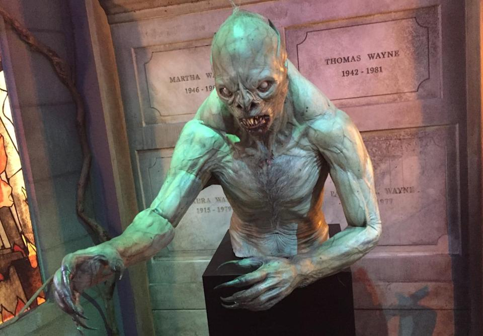 <p>This freaky prop appears in one of Bruce Wayne's visions. Behind the creature are the tombs of Bruce's parents, Martha and Thomas, and grandparents Laura and Patrick. </p>