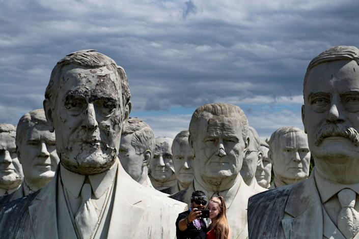 A couple poses for a selfie with giant salvaged busts of former US Presidents August 25, 2019, in Williamsburg, Virginia. (Photo: Brendan Smialowski/AFP/Getty Images)