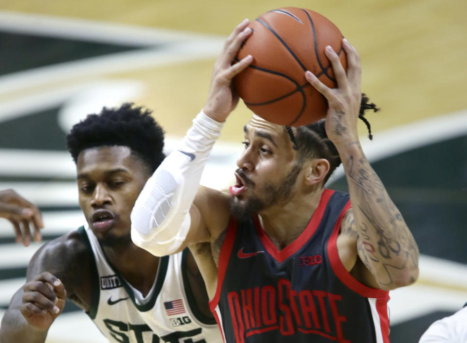 Ohio State guard Duane Washington Jr. drives to the basket against Michigan State guard Rocket Watts during the first half of an NCAA college basketball game Thursday, Feb. 25, 2021, in East Lansing, Mich. (AP Photo/Duane Burleson)