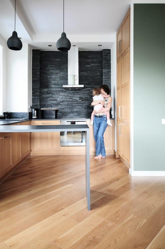 "<p>A traditional-meets-modern look was chosen for the <a rel=""nofollow"" href=""https://www.homify.co.uk/rooms/kitchen"">kitchen</a>. High wood cabinets ensure a solid yet subtle look, while the stainless steel peninsula incorporates a bit of shine.</p><p>And the diagonally placed wooden floors and artistic ceiling pendants? Well, that's just creative design!</p>  Credits: homify / IDeALS 
