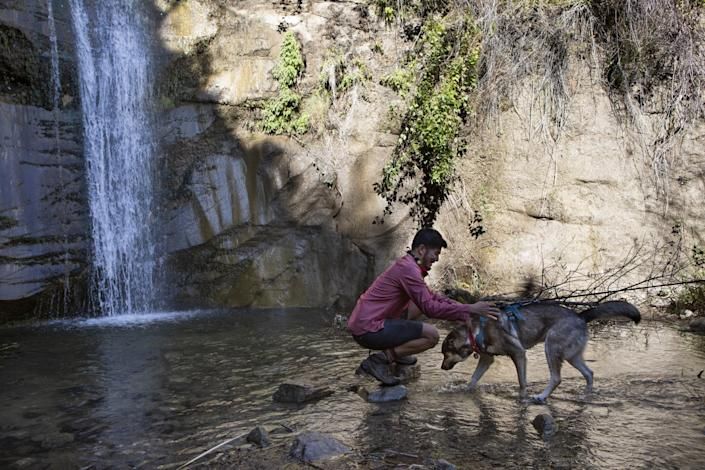 Near a waterfall and a rock wall, a man kneels on rocks in shallow water with his dog.