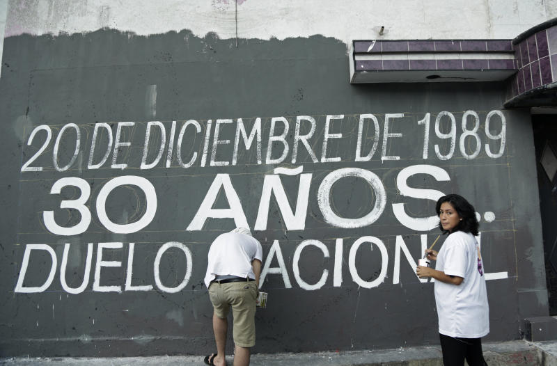 """In this Dec. 15, 2019 photo, activists paint a the Spanish message: """"Dec. 20, 1989. 30 years. National Day of Mourning,"""" ahead of the 30th anniversary of U.S. invasion of Panama in the El Chorrillo neighborhood where former Gen. Manuel A. Noriega operated his headquarters and is an area that was bombed during the invasion in Panama City. This week relatives won a victory when the government declared Friday, Dec. 20, 2019 a day of national mourning for the first time. (AP Photo/Arnulfo Franco)"""