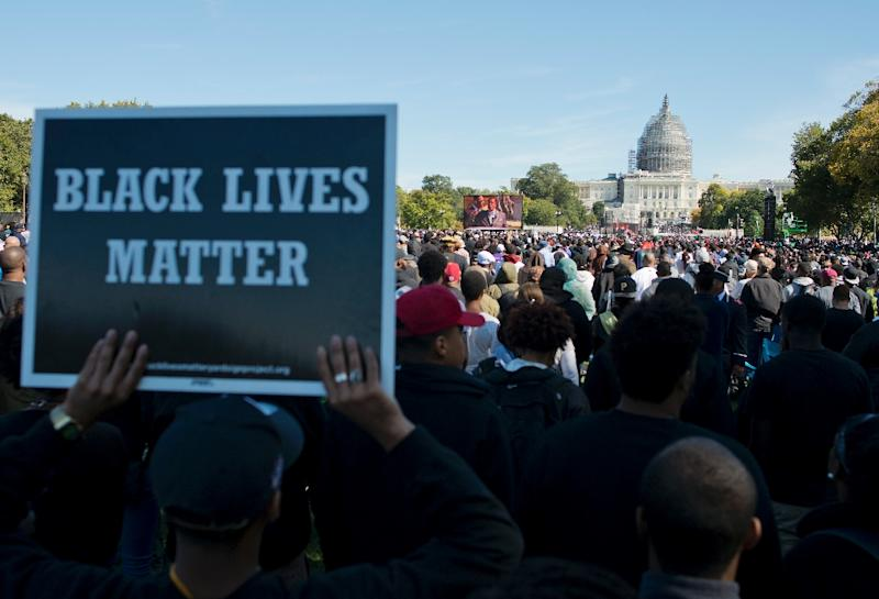People listen to speeches during the Justice or Else! rally on the National Mall in Washington, DC on October 10, 2015 (AFP Photo/Andrew Caballero-Reynolds)