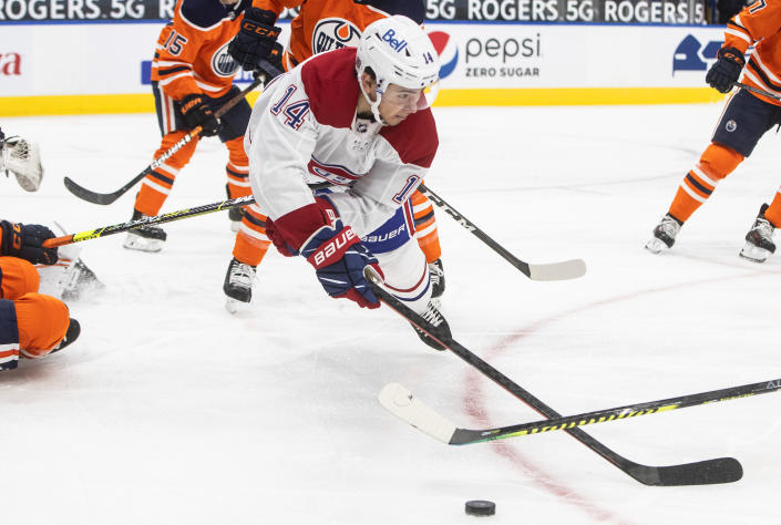 Montreal Canadiens' Nick Suzuki (14) dives for the puck against the Edmonton Oilers during first-period NHL hockey game action in Edmonton, Alberta, Saturday, Jan. 16, 2021. (Jason Franson/The Canadian Press via AP)