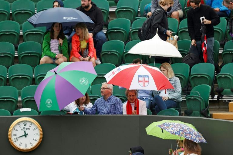 Rain pain: Spectators shelter from the rain beneath umbrellas as they wait for play to begin on the first day of Wimbledon