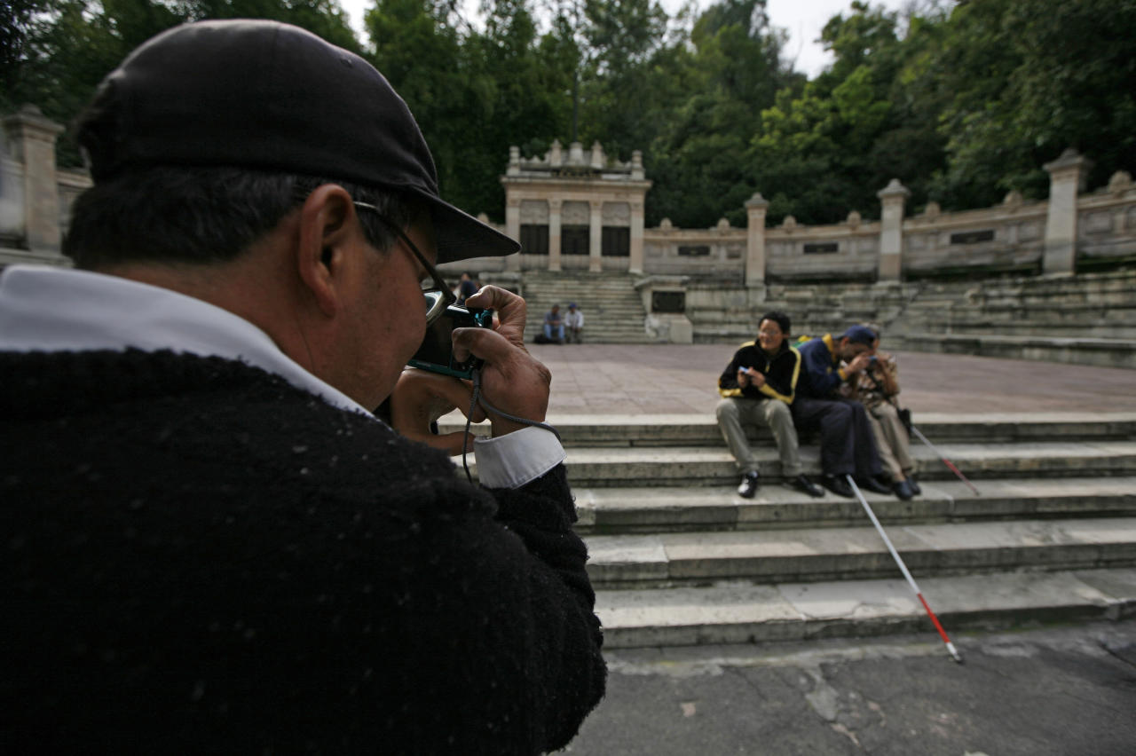 In this photo taken Sept. 7, 2011, Rodrigo Telon Yucute, a former guerrilla fighter during the civil war in the 1980's in his home country of Guatemala who lost his left forearm and his eyesight was destroyed after a land mine exploded beneath him, prepares to take a photograph of fellow blind friends at a park in Mexico City. He is one of 30 visually impaired or blind people learning photography with the help of the Mexico City foundation Ojos Que Sienten, or Eyes That Feel. (AP Photo/Marco Ugarte)