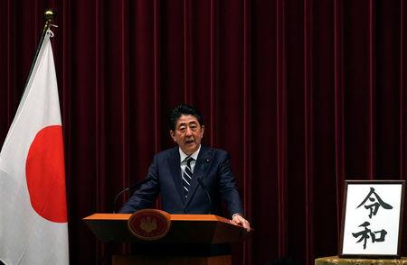 Japan's Prime Minister Shinzo Abe delivers a press conference standing next to the calligraphy 'Reiwa' which was chosen as the new era name at the prime minister's office in Tokyo