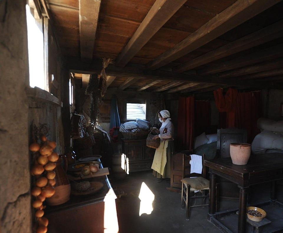 Scenes from the Pilgrim Village at Plimoth Patuxet living museum. An interpreter, wearing a mask due to COVID-19, works in a replica of a Pilgrim house.