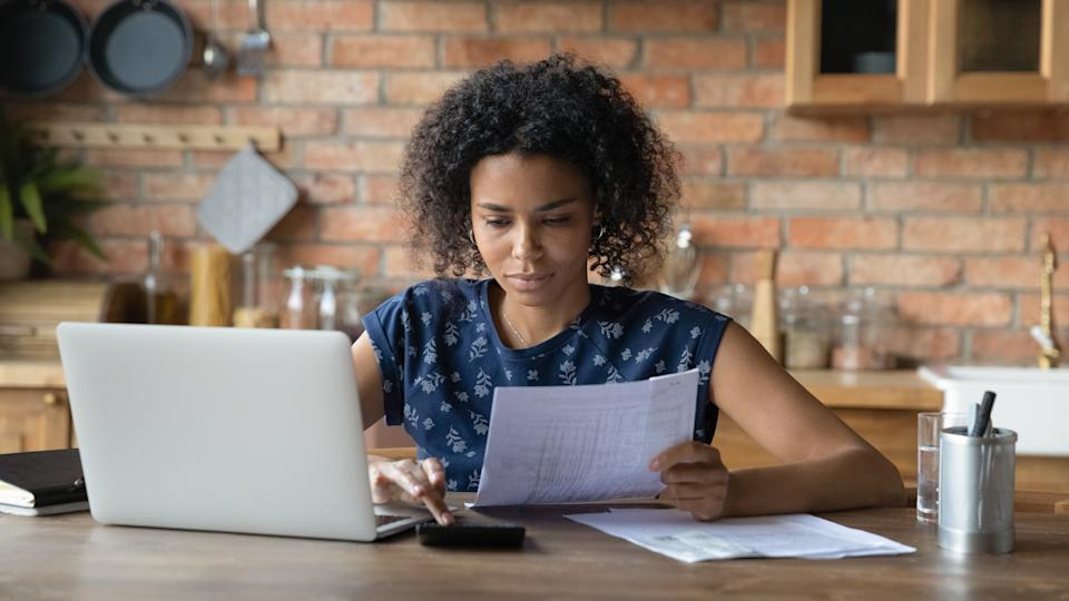 Serious millennial biracial woman calculate household expenditures finances on calculator at home. Focused African American wife pay bills taxes online on laptop, manage family finances or budget.