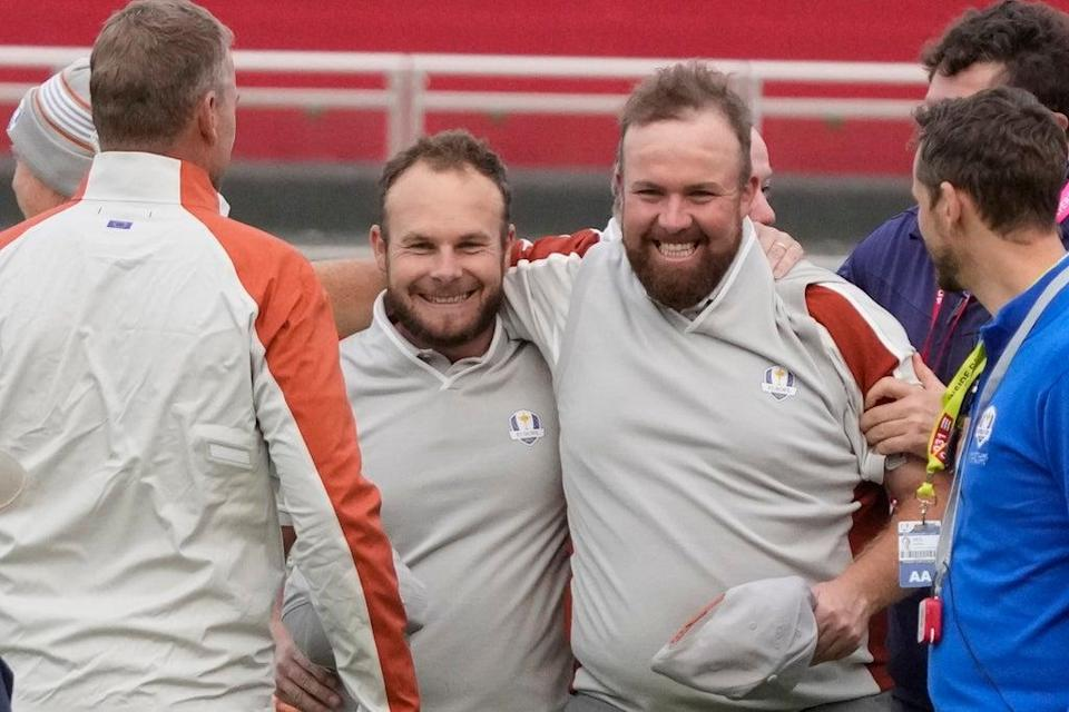 Shane Lowry and Tyrrell Hatton celebrate on the 18th hole after winning their four-ball match on day two of the Ryder Cup (Charlie Neibergall/AP) (AP)