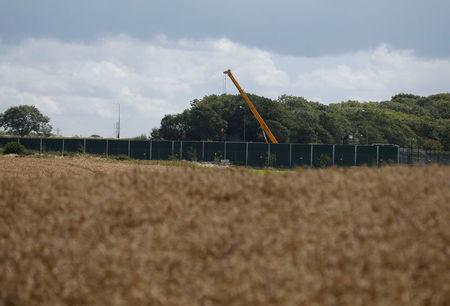 FILE PHOTO: A crane opertates behind barriers at Cuadrilla's Preston New Road fracking site near Blackpool