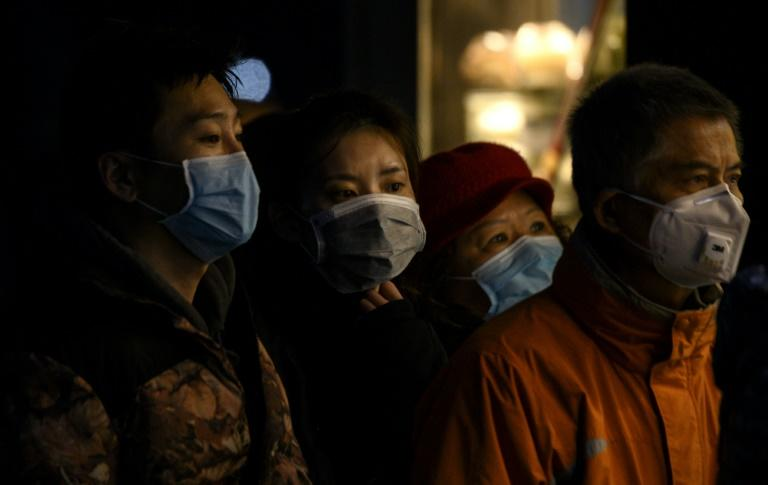 People wearing protective facemasks queue to order food in Shanghai -- the scale of the novel coronavirus epidemic has swelled after authorities in central Hubei province, the epicentre of the contagion, changed the criteria for counting cases